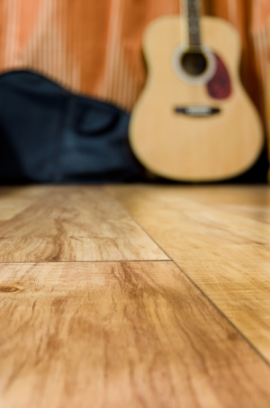 acoustic quitar in a room with wooden floor